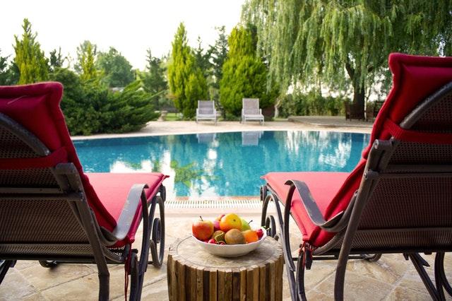 červená lehátka připravená u bazénu k relaxaci