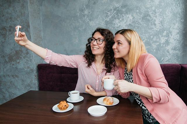 dvě ženy se fotí mobilem